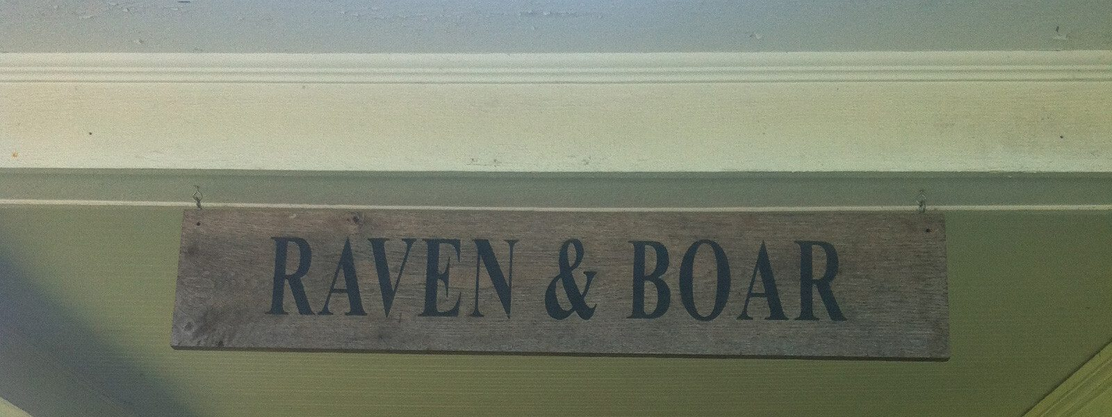 """Wooden sign with text """"Raven & Boar."""""""