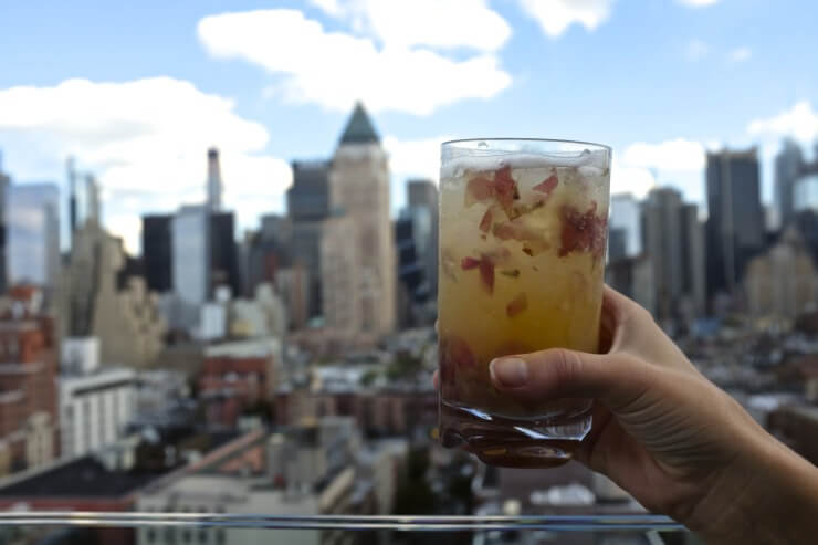 Hand holding Los Andes cocktail with Manhattan skyline in background.