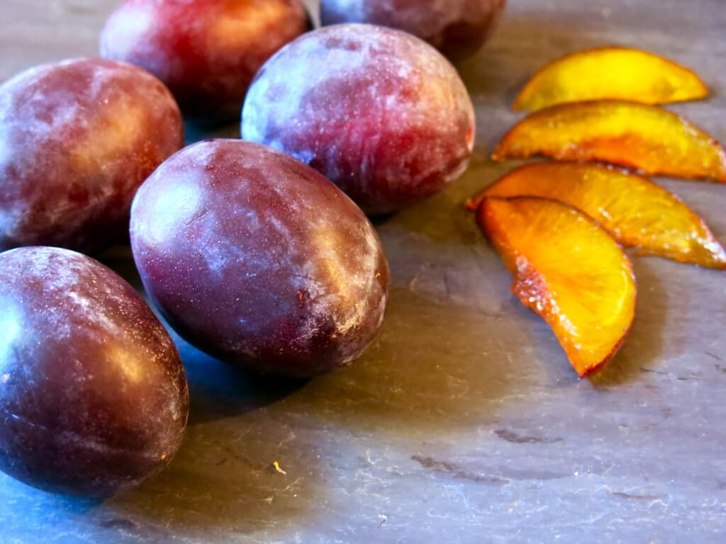 Whole and sliced plums.