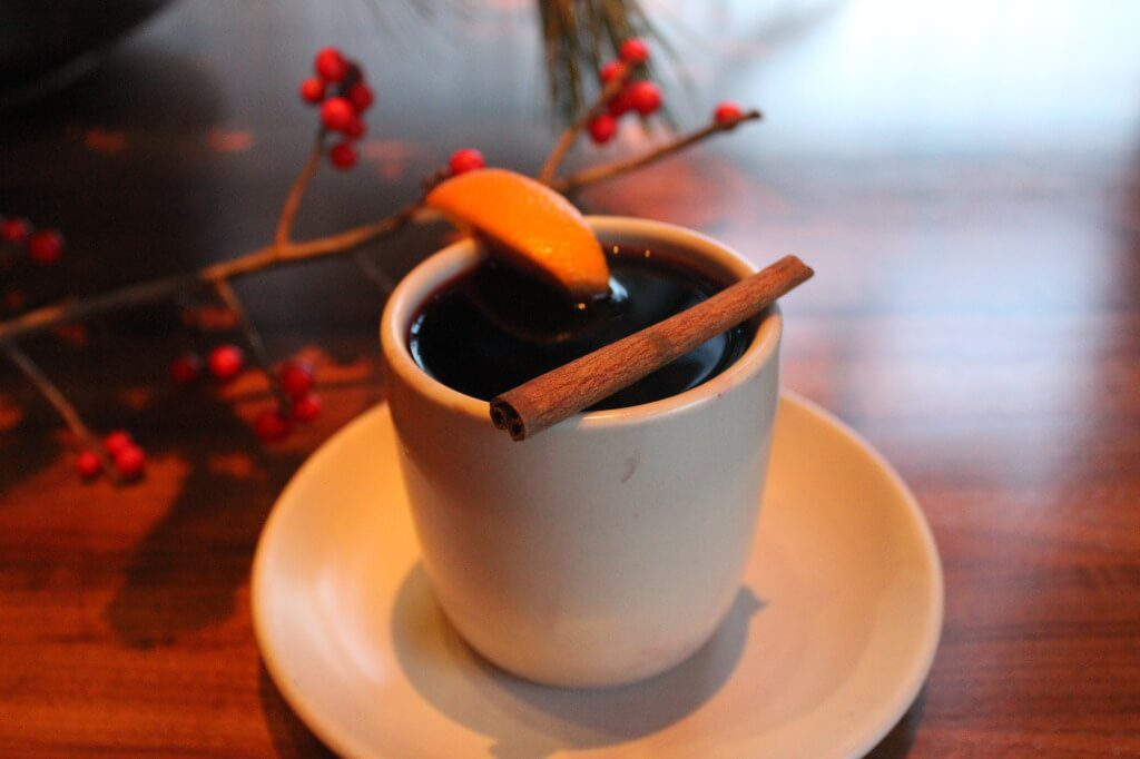 Cup of mulled wine with citrus wedge and cinnamon stick.