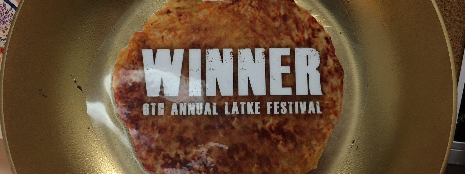 "Potato pancake with text ""Winner 6th Annual Latke Festival."""