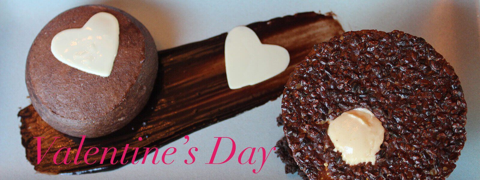 """Plated chocolate dessert with white chocolate hearts and text """"Valentine's Day."""""""