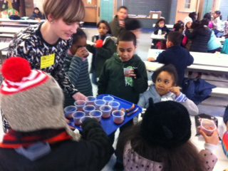 Meghan handing out cups of carrot juice to students.