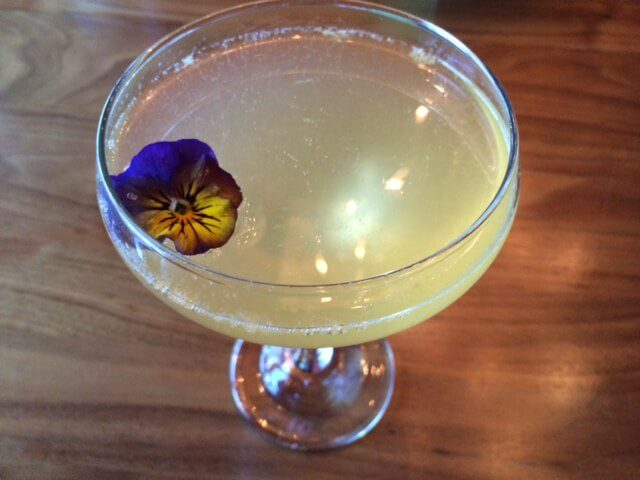 The Paramour cocktail in a coupe glass topped with a violet.