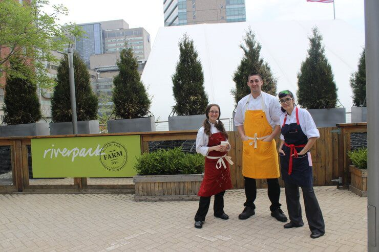 Chefs Emily Wallendjack, Brian Del Colle, and Miriam Schine posing for photo with Riverpark sign in background.