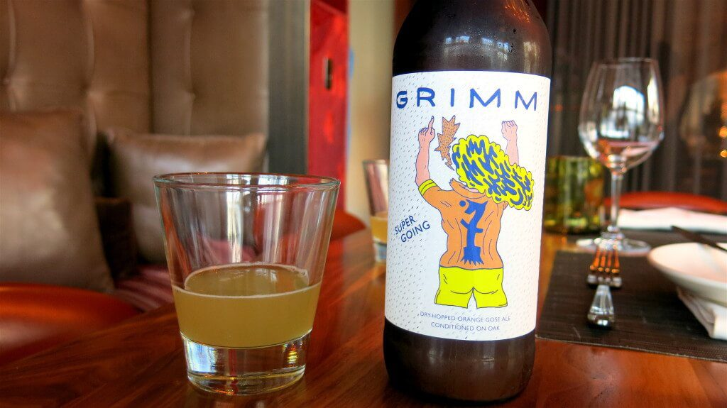 Bottle of Grimm Beer and small glass with beer.