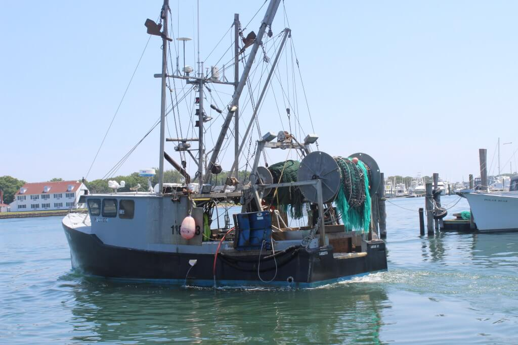 Fishing trawler pulling out from a dock.