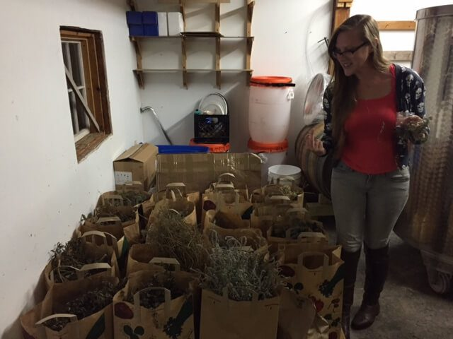 Bianca with many paper bags of botanicals for infusing.