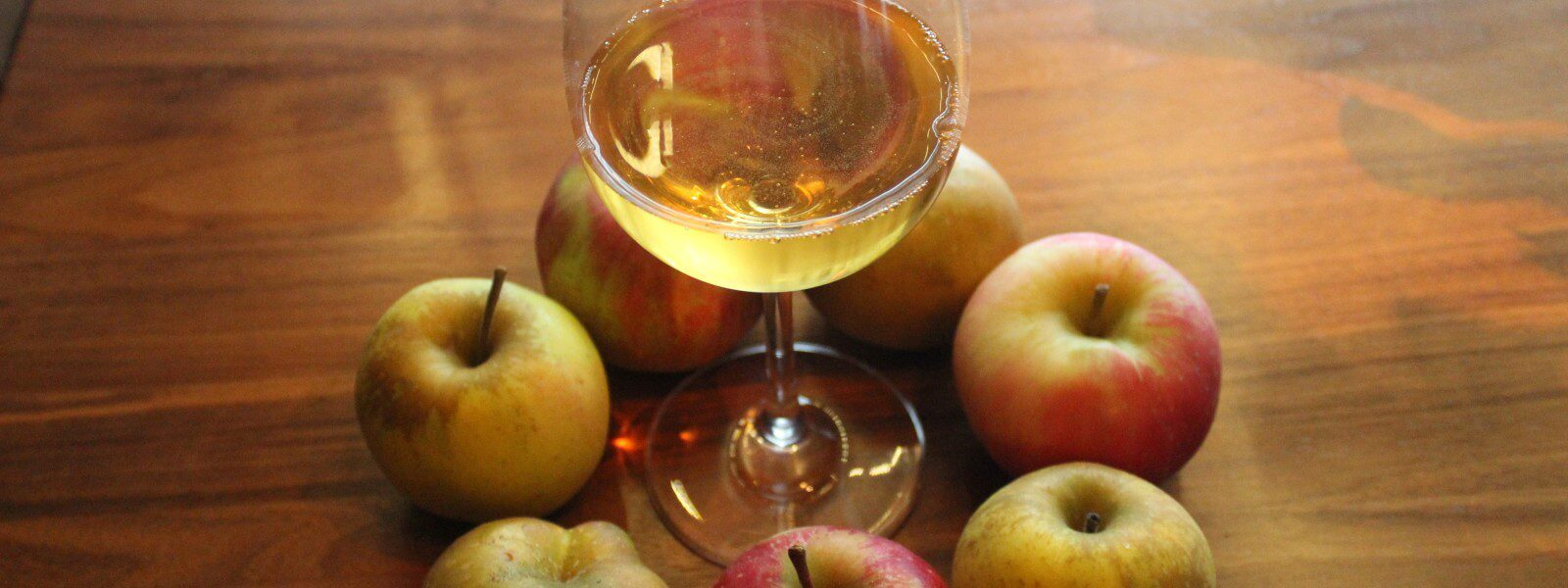 7 apples surrounding a glass of cider.