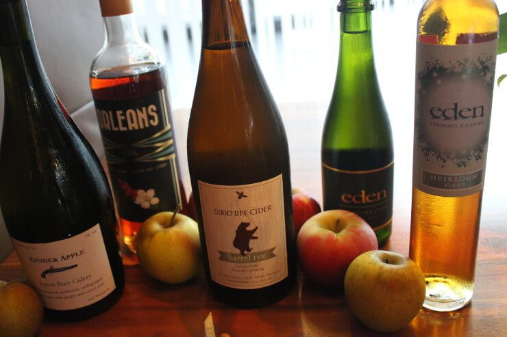 5 bottles of different cider and apples.