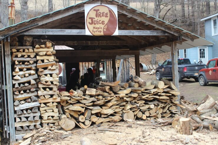 "Stacks of firewood under a ""Tree Juice Maple Syrup"" sign."