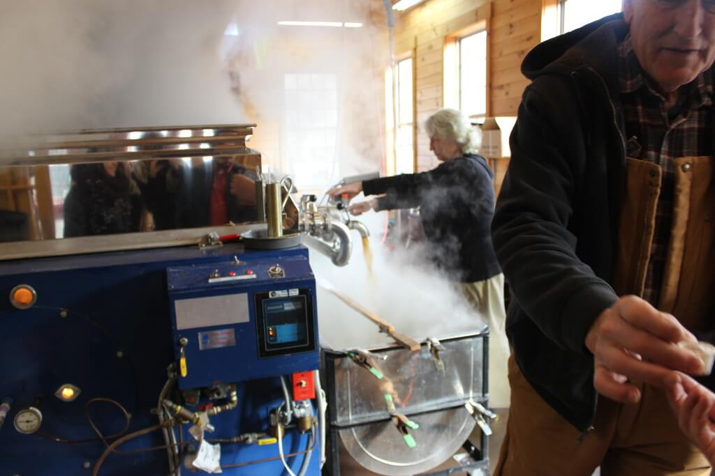 Person stirring maple syrup in vat in the sugar shack.