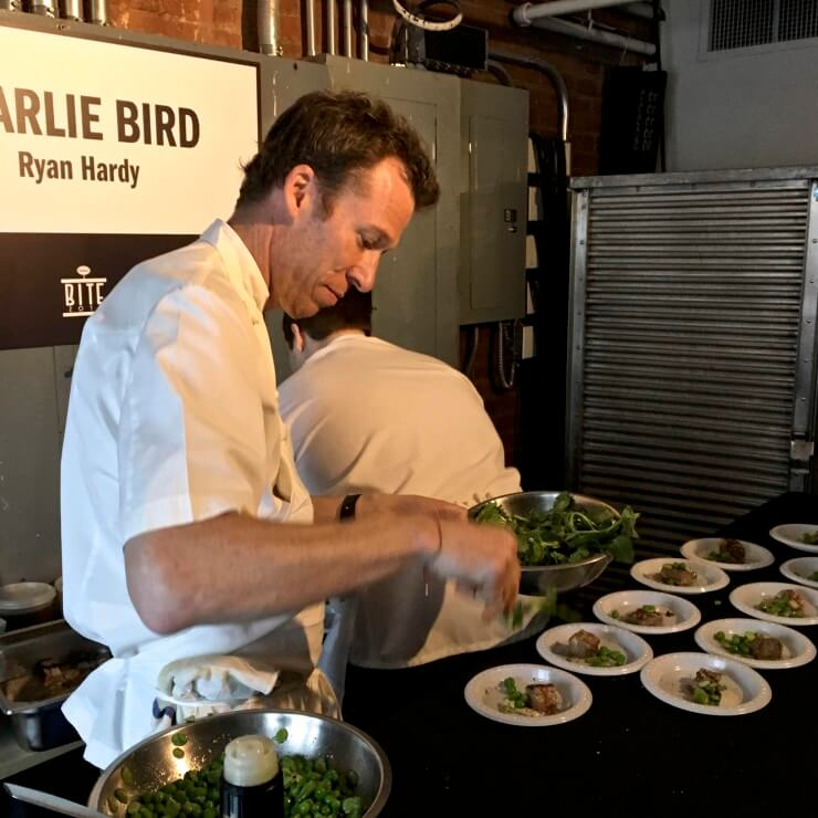Chef Ryan Hardy plating Sous Vide Lamb Breast, with Fava Beans, Pea Greens, and Black Sesame Puree.
