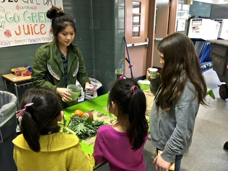 Students getting cups of green juice.