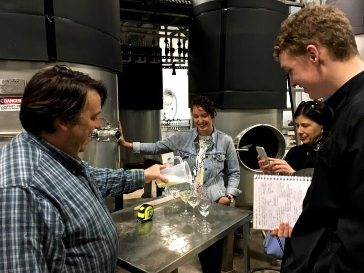 4 people in the barrel room, with bläufrankisch being poured into wine glasses.