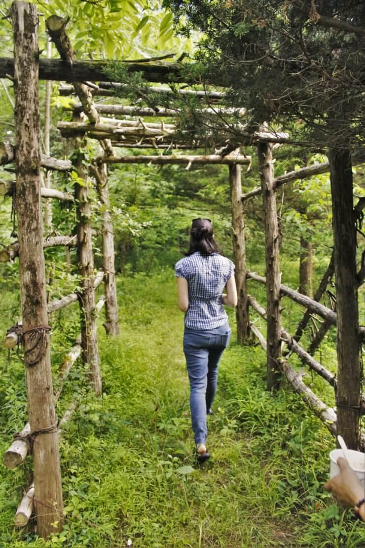 Woman walking through wooden beam structure.