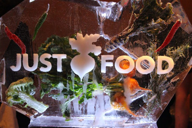 "Ice sculpture with vegetables inside and ""Just Food"" etched on the front."