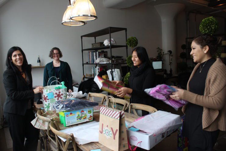4 PRINT team members wrapping presents at a table spread with gift wrap.