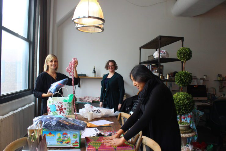 3 PRINT team members at the wrapping table.