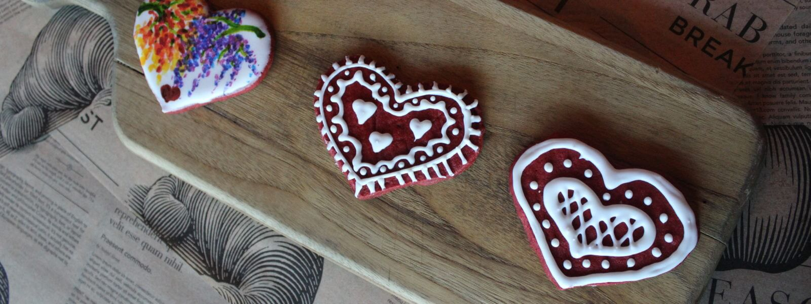 3 heart-shaped decorated cookies on a board.