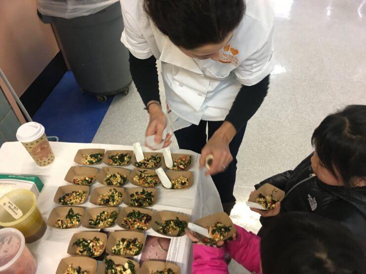 Children taking servings of rainbow crunchy salad.