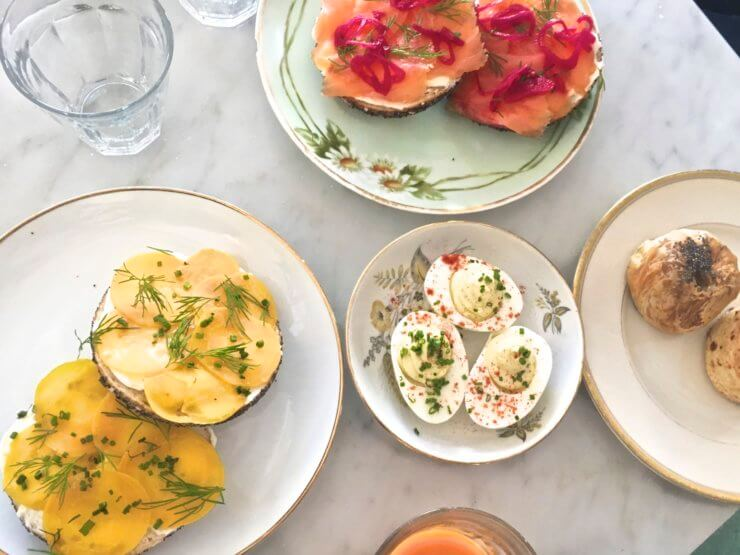 20th Century Cafe spread of open face bagels, deviled eggs, poppy seed pierogi with sour cherry jam, potato knish, and lardon scones.