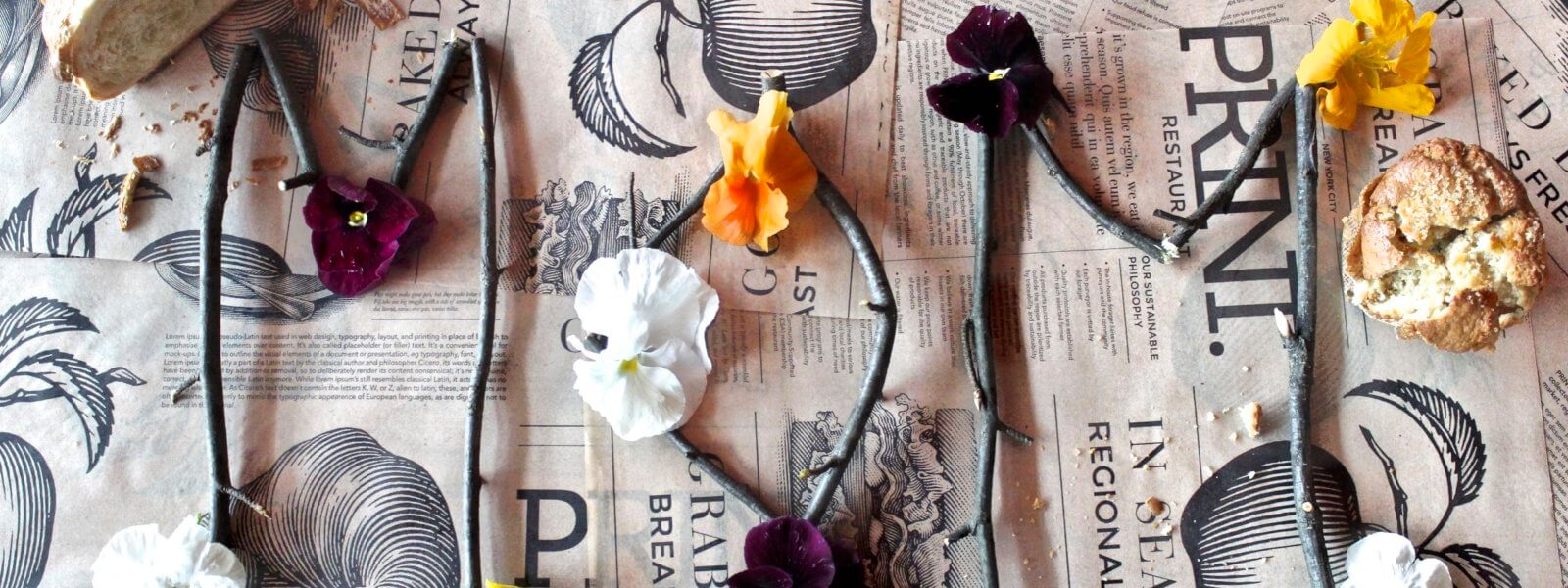 """Mom"" spelled out with twigs and flowers on PRINT paper."