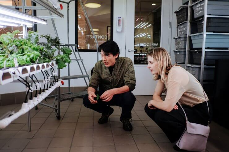 An ICE student showing Meghan the hydroponic workings.