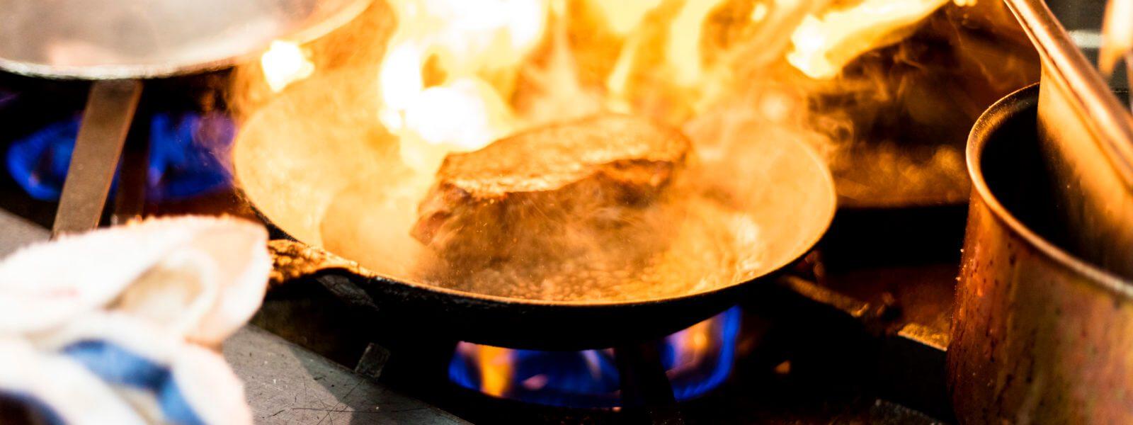 Steak flambéed in saute pan.