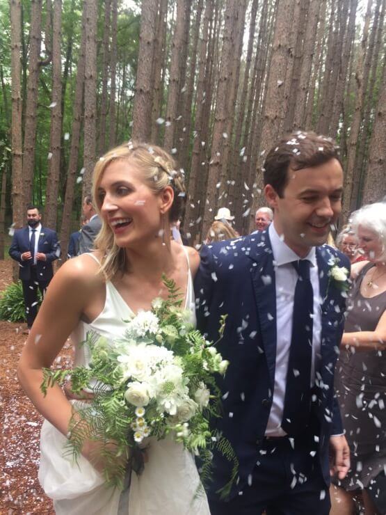 Meghan and Jeffrey walking back up the aisle, showered in flower petals.