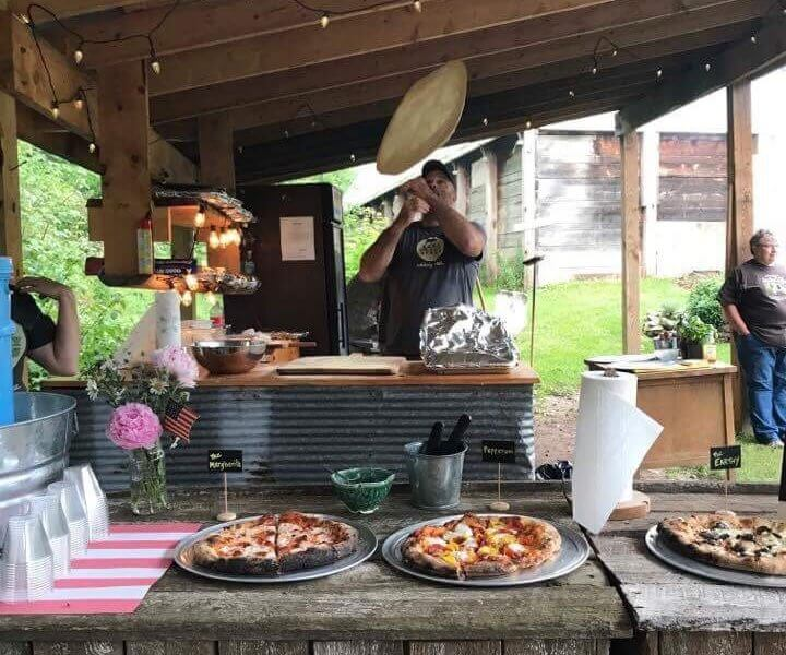 Man tossing pizza crust in the air with prepared pizzas in the foreground.