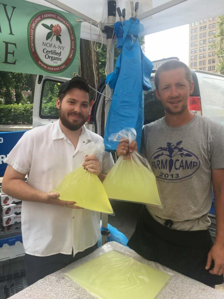 A chef and vendor holding bags of whey.