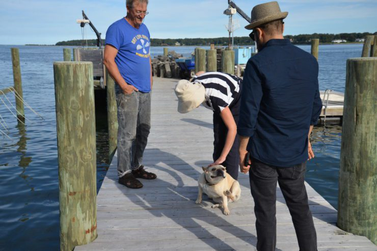 Michael and his dog with PRINT team members on the dock.