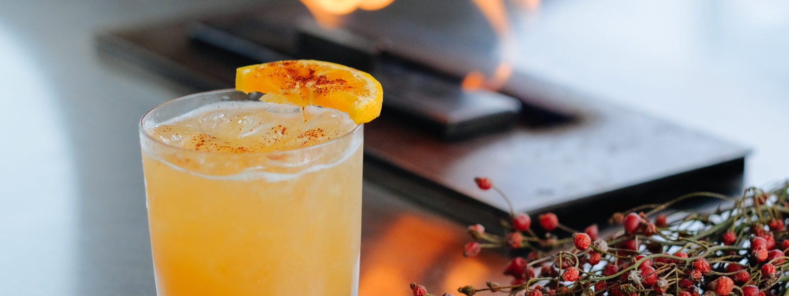 Cocktail with orange slice in front of fire orb, with holly berries.