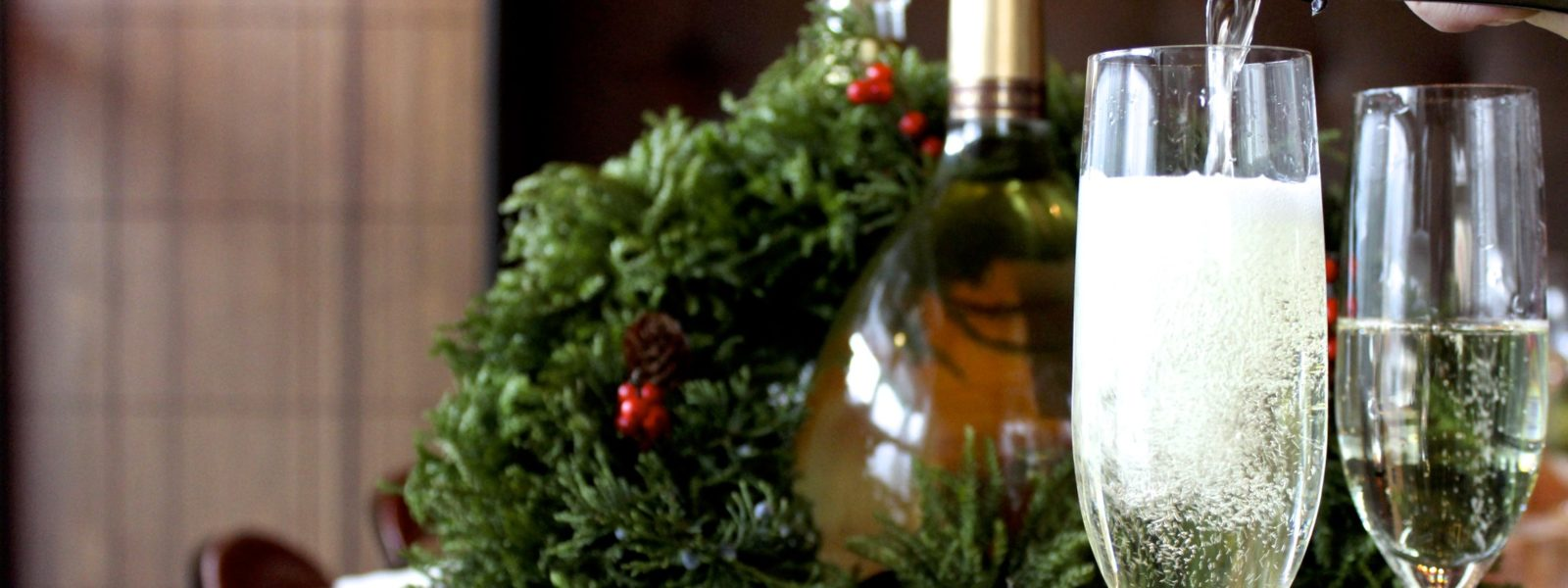 A Christmas wreath around a bottle of wine, and two champagne flutes being filled.