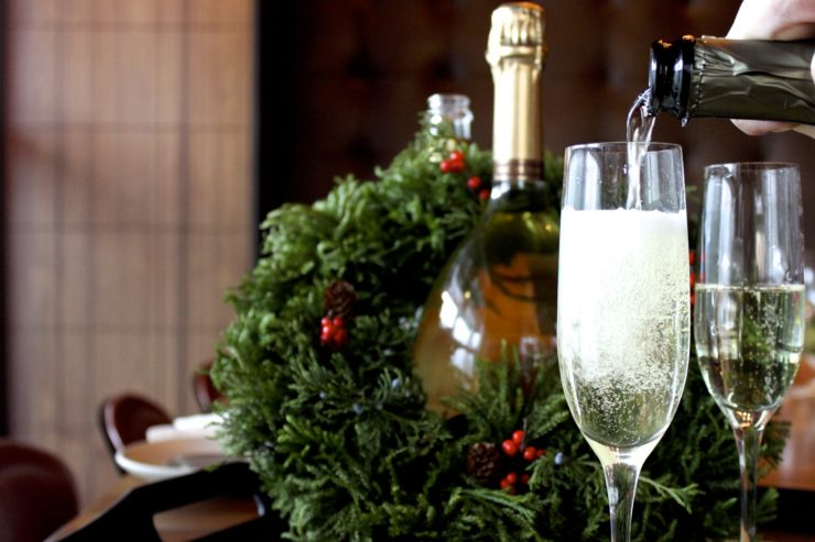Champagne being poured into glass with bottle and wreath in background.