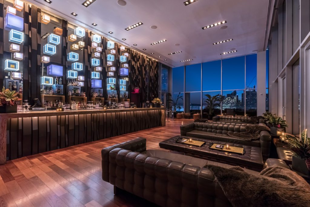 Interior of The Press Lounge featuring the bar and leather couches.