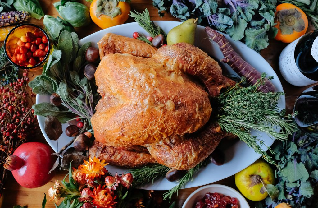 Overhead shot of turkey filled with herbs and surrounded by fresh produce.