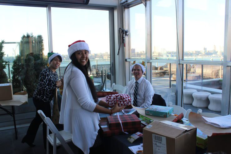 PRINT team members wrapping gifts and wearing holiday hats.