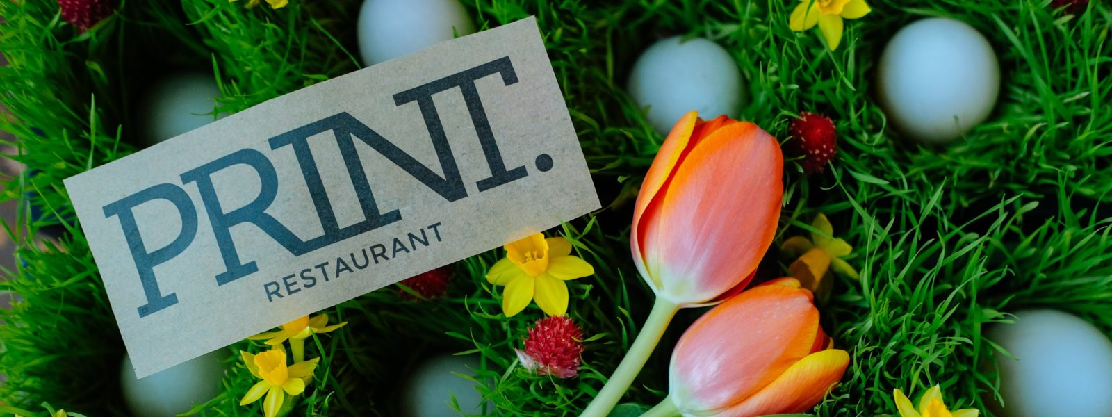 PRINT logo on paper with tulips and blue eggs.