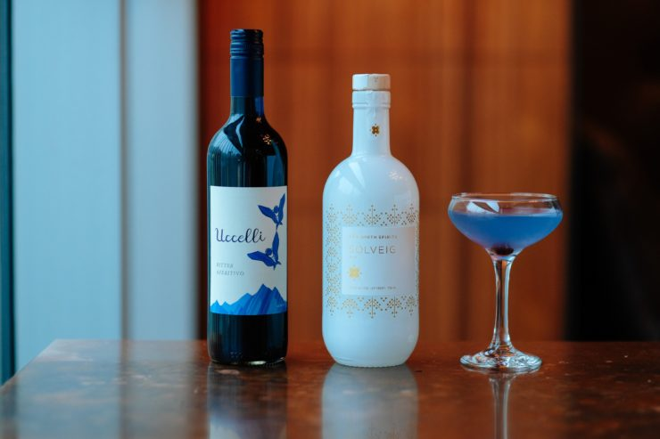 Violet Hour cocktail, bottle of Uccelli and bottle of Solveig.
