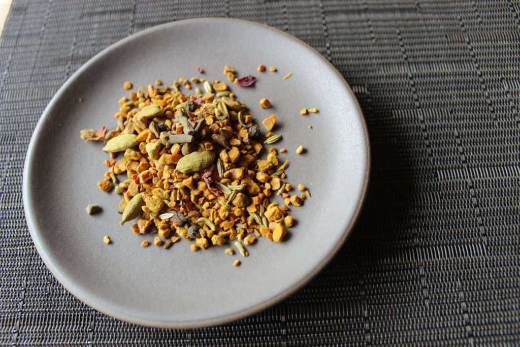 Loose turmeric chai blend on a plate.
