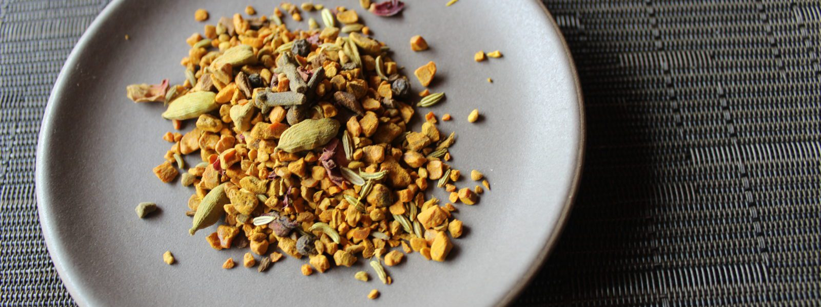 Loose turmeric chai blend on a plate.