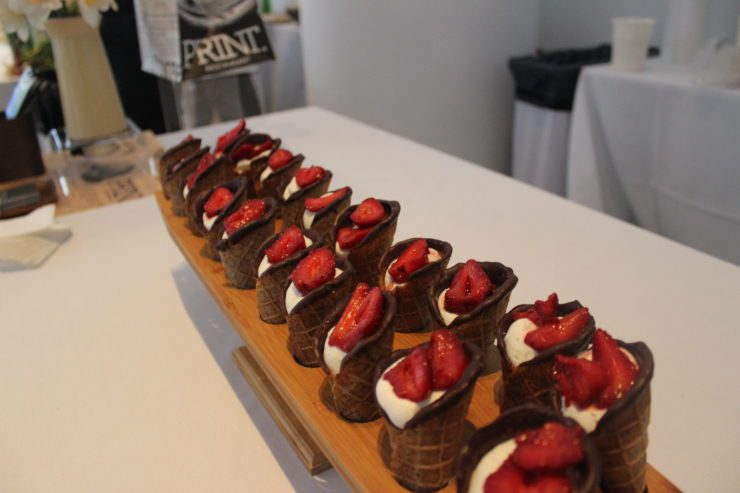 Chocolate-dipped buckwheat waffle cones with coriander cream and macerated strawberries.