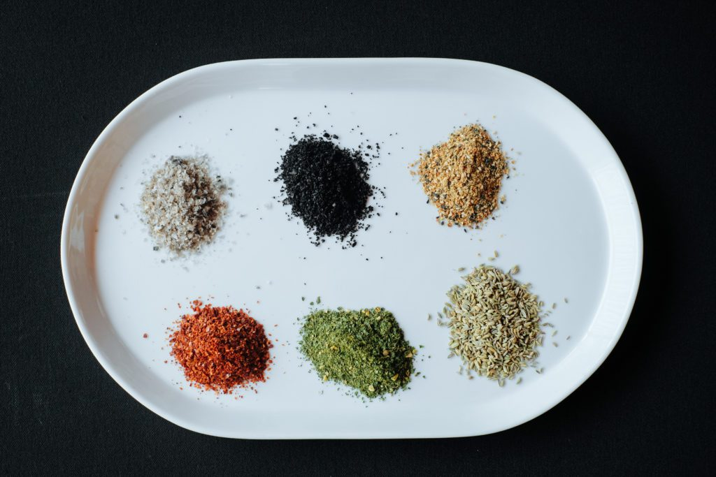 White plate with 6 piles of ground spices.