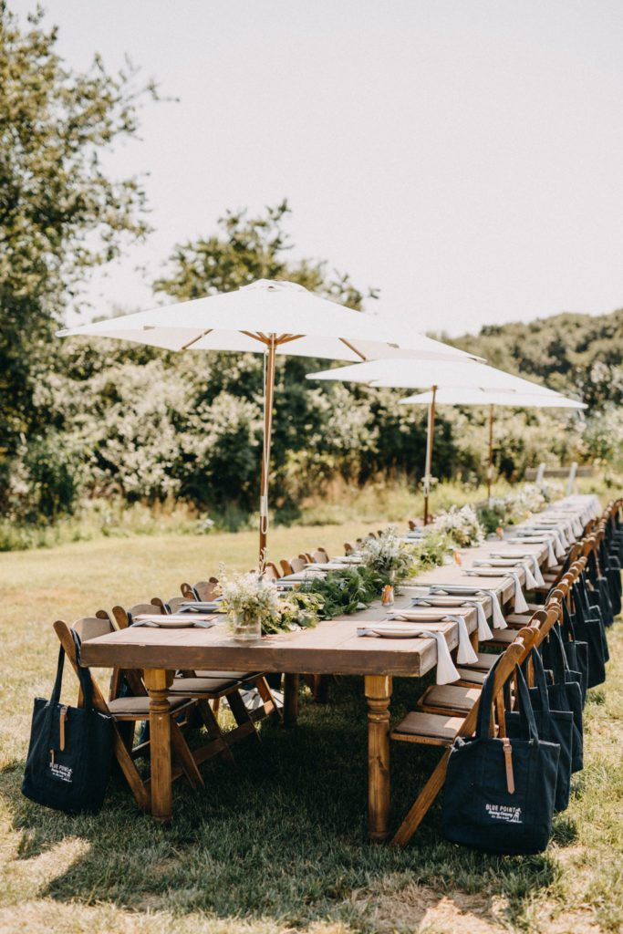 Long table set up in a field for dining with umbrella.