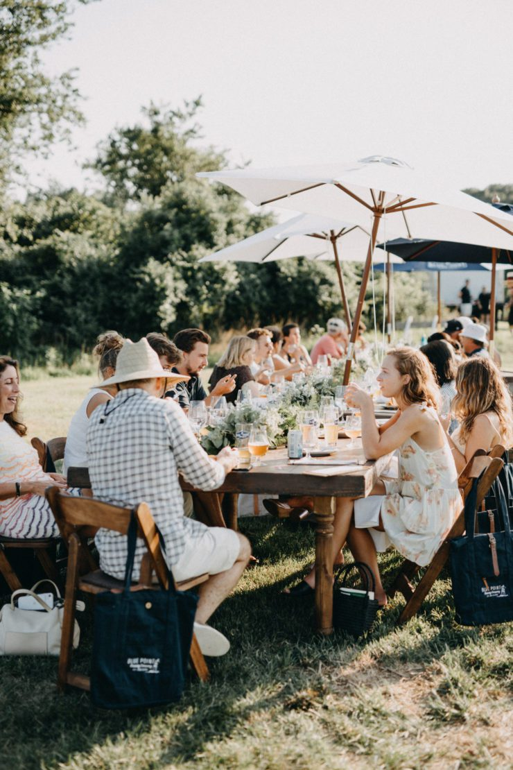 Dining table in a field filled with people enjoying dinner.