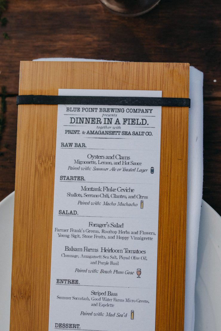 Dinner in a Field menu on board with place setting.
