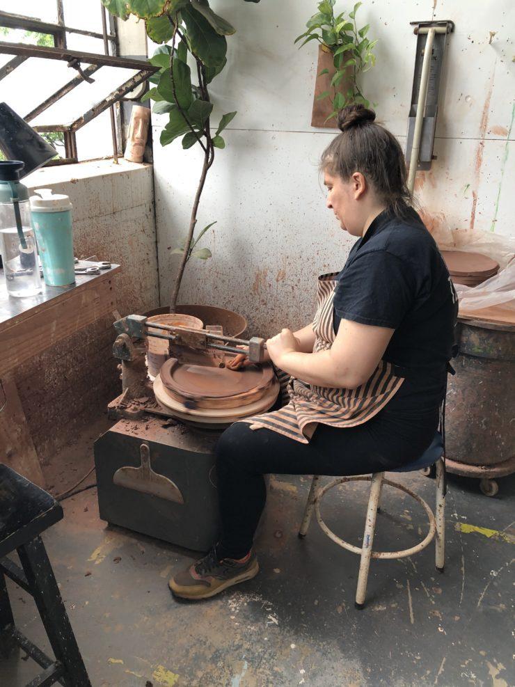 Artisan at work on ceramic serving piece.