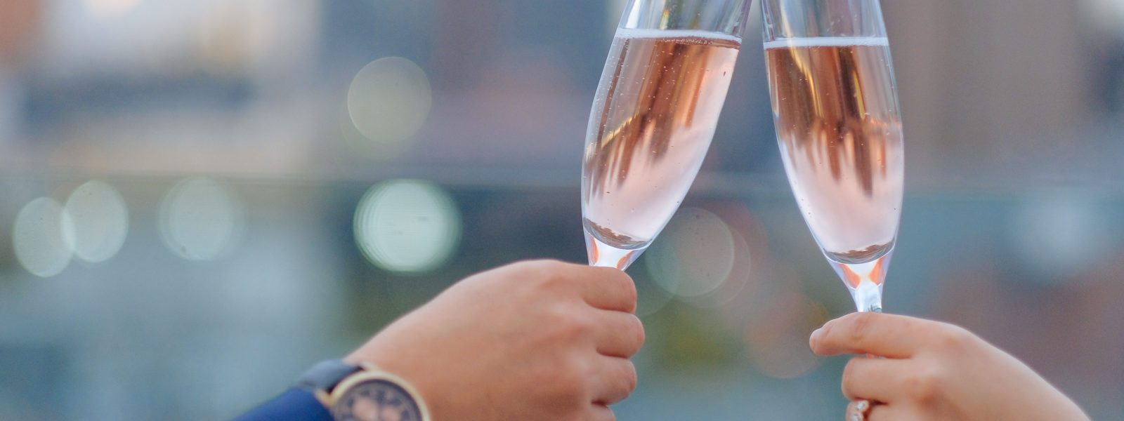 Two hands toasting with rosé in champagne flutes.